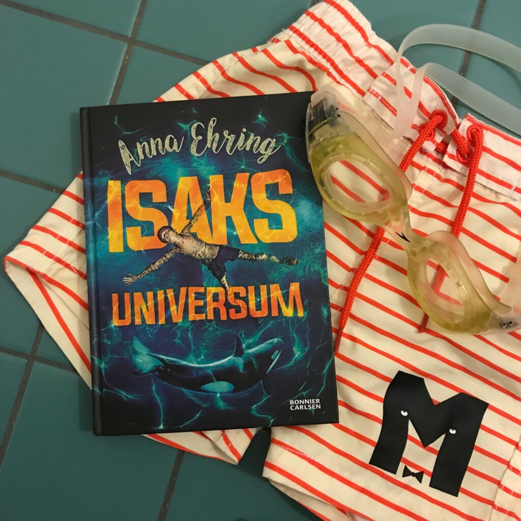 """Barnboken """"Isaks universum"""" av Anna Ehring tillsammans med badshorts från Mini Rodini."""